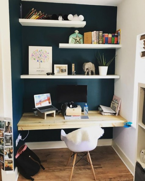 a navy painted niche, white floating shelves, a floating wooden desk and a white chair will make up a small yet comfy nook
