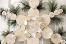 20 a snowy wood slice snowflake Christmas wreath with evergreens is a nice idea to decorate a door instead of a usual wreath