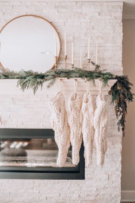 evergreens, simple candles in gold candleholders and white knit stockings on the mantel for a minimal holiday look
