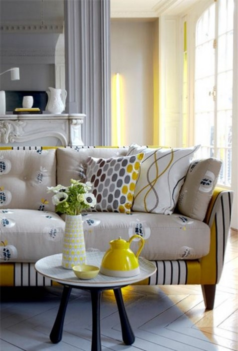 a bright sofa with a yellow striped base and neutral cushions and pillows with a fruit print is a fun and quirky idea to go for