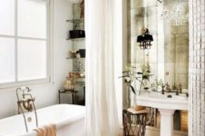21 a refined Parisian bathroom with a mirror wall, a crystal chandelier, a tub, open shelves and a sink