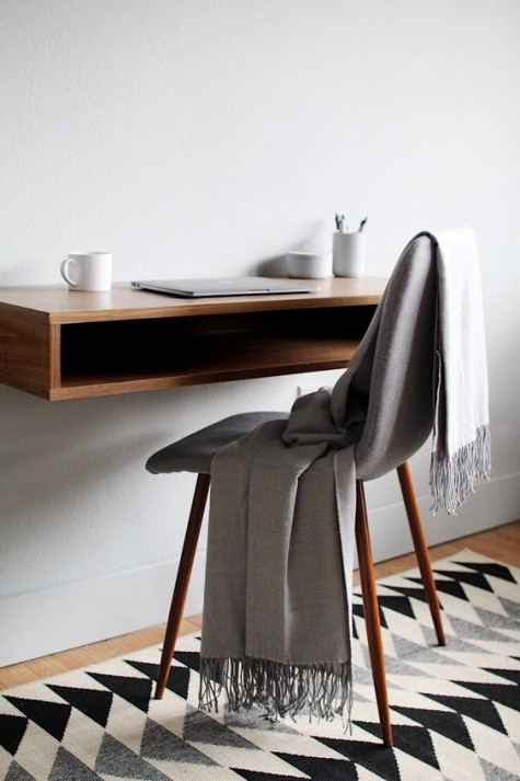 a stylish floating mini desk with some storage space inside and a chair on tall wooden legs is ideal for a small space
