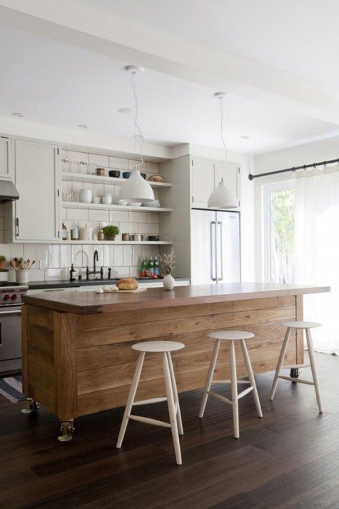 an off-white kitchen and a wood plank kitchen island that adds warmth to the space and contrasts its style