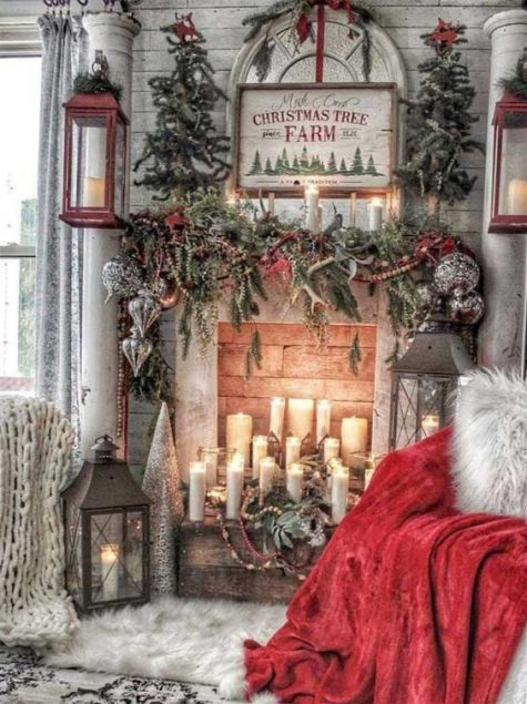 enchanting vintage Christmas decor with evergreens, candles, a red blanket, oversized candle lanterns and a vintage sign