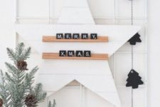 21 minimalist Christmas decor with a black tree garland, pale evergreens and pinecones, a star with scrabbles and a tag