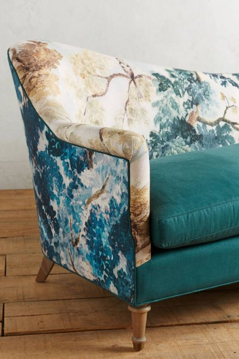a chic sofa with teal cushions and a seat, a botanical print seat and armrests plus wooden legs for a catchy touch in your living room