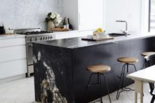 22 a minimalist white kitchen and a black marble kitchen island with a waterfall countertop to make a statement