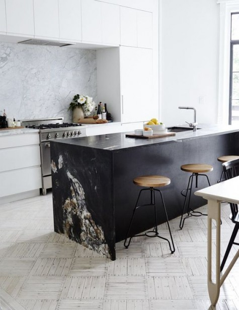 a minimalist white kitchen and a black marble kitchen island with a waterfall countertop to make a statement