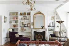 22 a vintage-infused Parisian living room with bold velvet furniture, chic chandeliers, a mahogany desk, a fireplace and some artworks