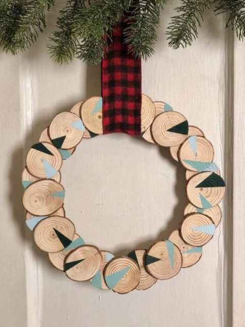 a wood slice Christmas wreath with geometric design and a plaid ribbon is a cool bold decoration idea