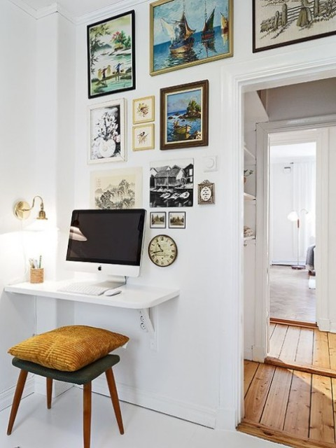 a white floating mini desk and a stool with a pillow, a gallery of artworks and a wall lamp for working