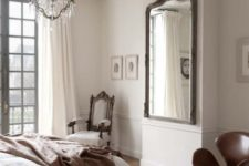 23 an elegant Parisian bedroom with a herringbone floor, a statement mirror, a chic crystal chandelier and a refined chair