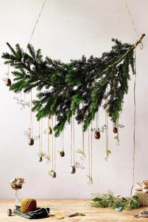 an evergreen branch with small vases and greenery in them is a stylish overhead Christmas decoration