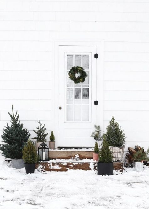minimalist Christmas outdoor decor with trees in pots and baskets plus candle lanterns is very up-to-date