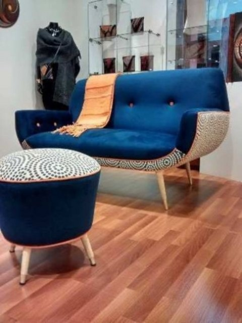 a mid-century modern loveseat with a navy top and a printed base and a matching footrest or ottoman