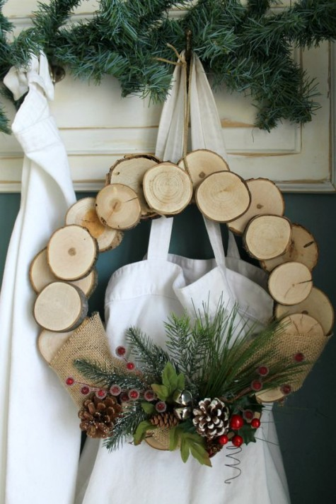 a wood slice wreath with fake greenery, berries, pinecones and jingle bells is very bright and cozy for Christmas