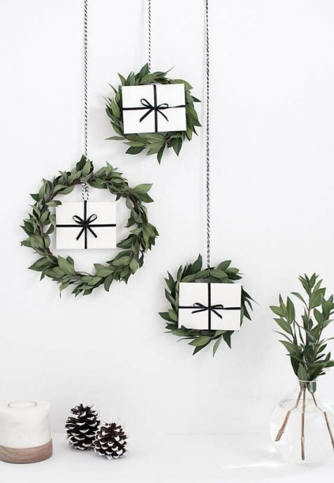 minimalist Christmas wreaths with white gift boxes inside hanging on the wall are super cool