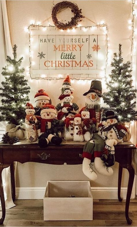 vintage Christmas decor with Christmas trees in burlap, pinecones, snowmen toys and a lit up Christmas sign