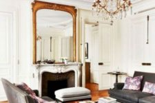 25 a refined Parisian living room with grey sofas, upholstered ottomans, a fireplace, a statement mirror and chandelier