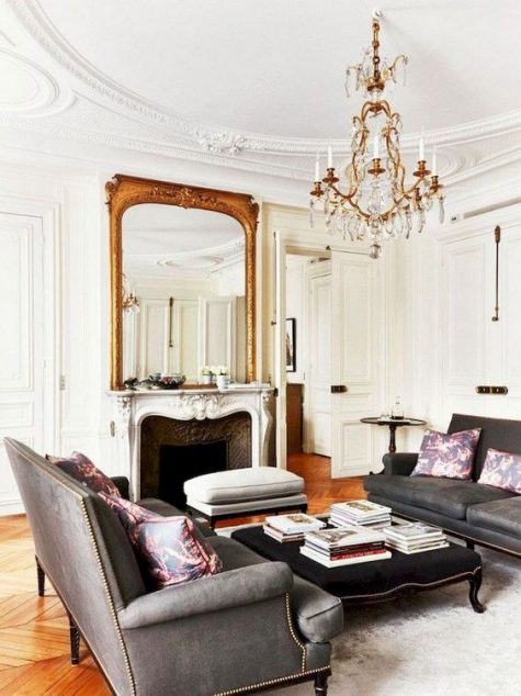 a refined Parisian living room with grey sofas, upholstered ottomans, a fireplace, a statement mirror and chandelier