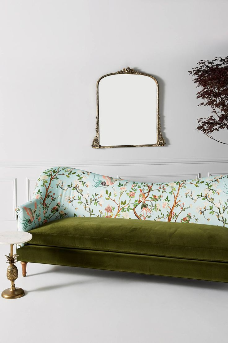 a refined mismatched upholstery sofa with a velvet green seat and a botanical and fauna print in blue on the back