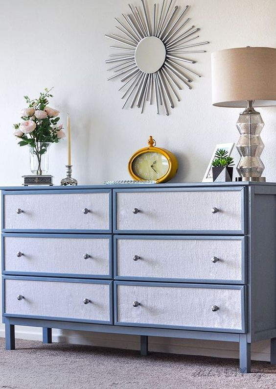 an IKEA Tarva hack painted blue and with blue contact paper and little geometric knobs for a chic look
