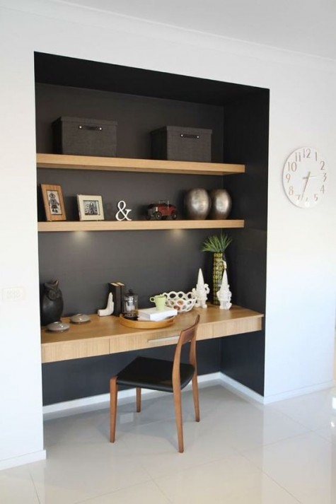 floating shelves and a floating desk with a drawer in a dark-colored niche withbuilt-in lights for working
