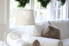 25 minimalist evergreen wreaths hanging on the windows look very chic and festive and don't bring excessive glitter or colors