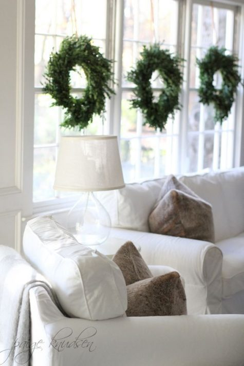minimalist evergreen wreaths hanging on the windows look very chic and festive and don't bring excessive glitter or colors
