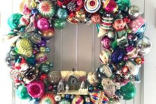 26 a vintage Christmas ornament wreath with a mini house is bright and bold and will catch everybody's eye
