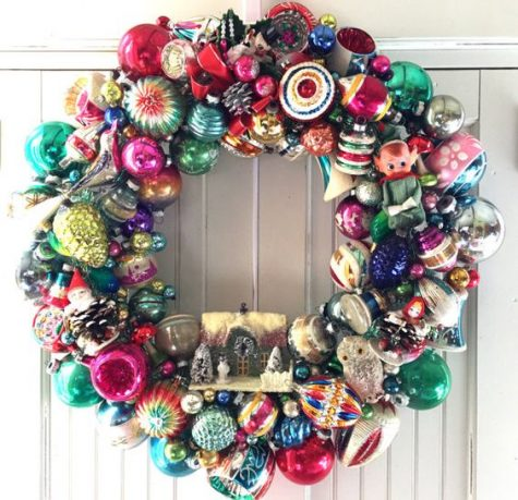 a vintage Christmas ornament wreath with a mini house is bright and bold and will catch everybody's eye