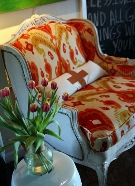 a vintage carved loveseat with neutral upholstery on the outside and bright abstract prints inside is a bold idea