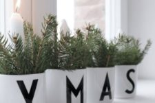 26 white pots with letters, candles and evergreens are cool to decorate a mantel or a windowsill