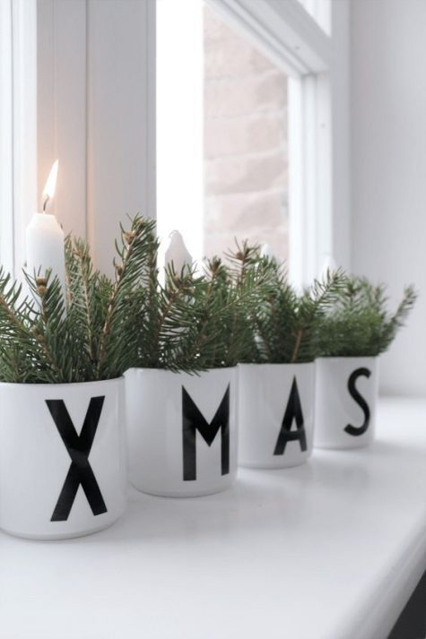 white pots with letters, candles and evergreens are cool to decorate a mantel or a windowsill