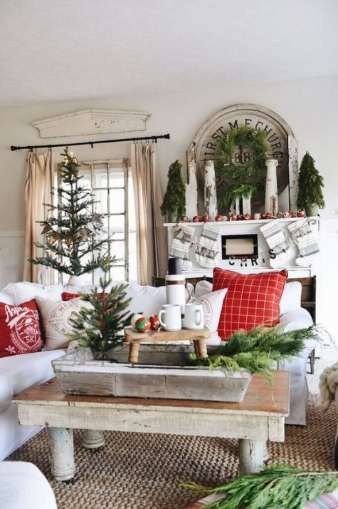 a bold farmhouse Christmas living room with a tree, mini trees, a wreath, colorful ornaments and wooden furniture