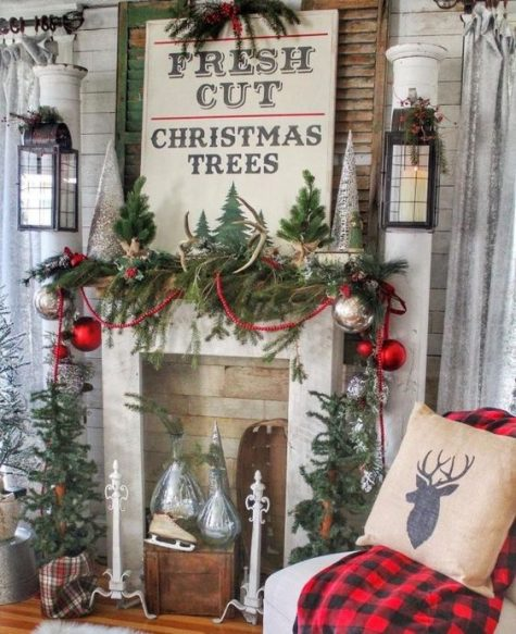 a bright farmhouse Christmas nook with evergreens, mini trees, silver and red ornaments, skis, signs and candle lanterns