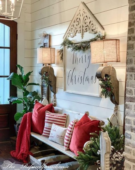 a bright farmhouse entryway with a sign, burlap lamps, red and striped pillows and evergreens