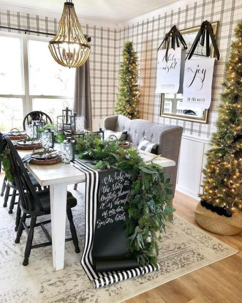 a chic farmhouse Christmas dining room with tall Christmas trees, a greenery runner, a striped and chalkboard runner, signs and candles