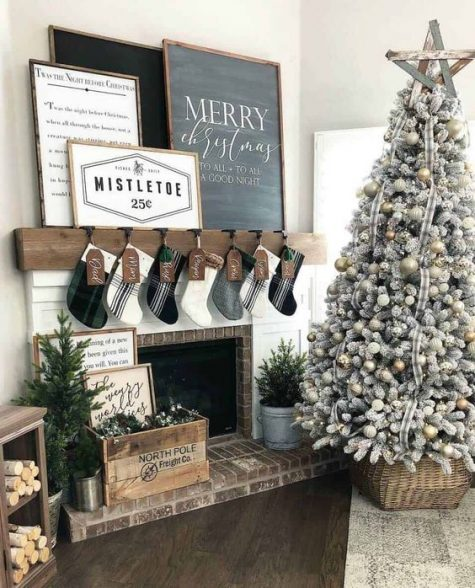 a cozy and chic farmhouse Christmas space with stockings, a neutral Christmas tree in a basket and artworks