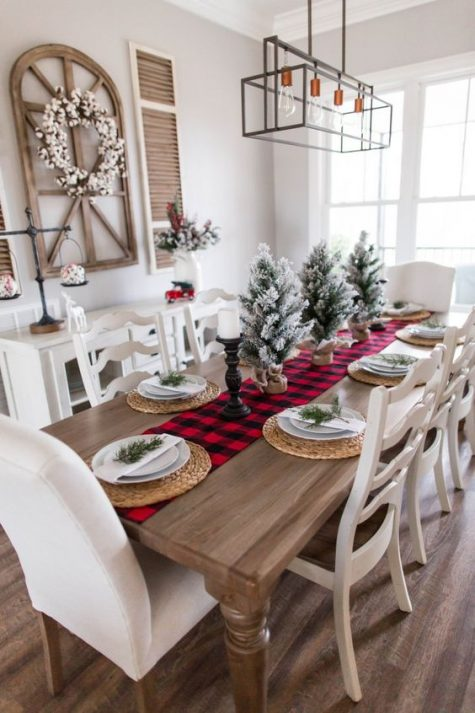 a farmhouse Christmas dining room with a cotton wreath, snowy Christmas trees, a plaid runner, candles and woven placemats