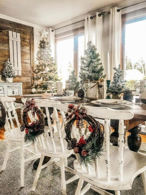 a farmhouse Christmas dining space with whitewashed chairs, snowy Christmas trees and pinecones