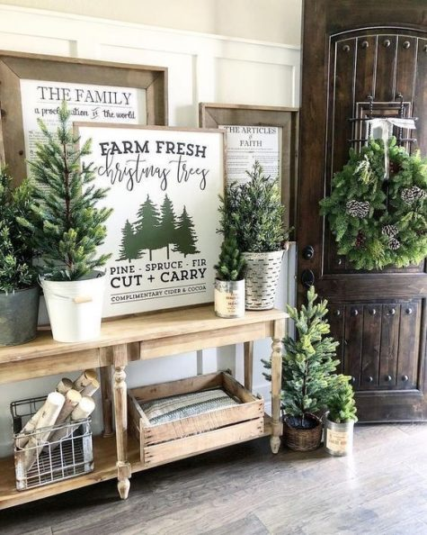 a farmhouse Christmas entryway with mini trees, an evergreen wreath with pinecones, firewood and signs