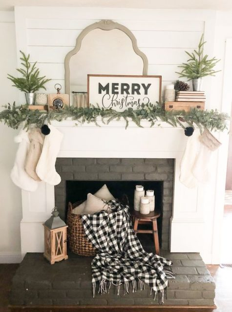 a farmhouse Christmas fireplace with evergreens, mini trees, a sgin, some stockings and a plaid blanket