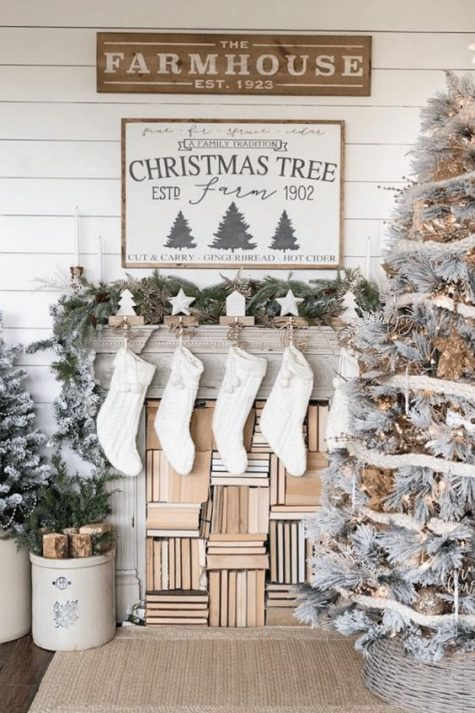 a farmhouse Christmas living room with a snowy Christmas tree with lights, knit stockings, mini trees and signs over the mantel