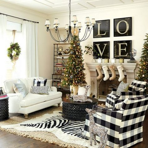 a farmhouse Christmas living room with a tree with lights and ornaments, buffalo check chairs and pillows, stockings