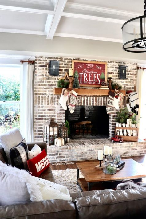 a farmhouse Christmas living room with colorful stockigns, candle lanterns, firewood, mini trees and plaid pillows