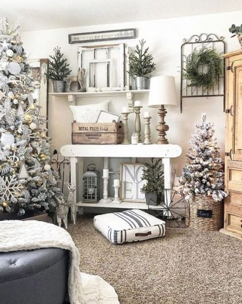 a farmhouse Christmas living room with snowy trees with lights and ornaments, mini trees, candles and lamps