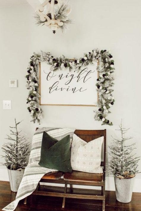 a farmhouse Christmas space with a snowy evergreen garland, snowy Christmas trees, a green and white pillow and a cozy blanket