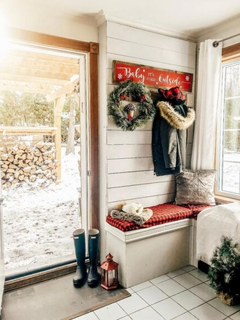 a farmhouse entryway with red plaid, evergreens, rubber boots and a candle lantern
