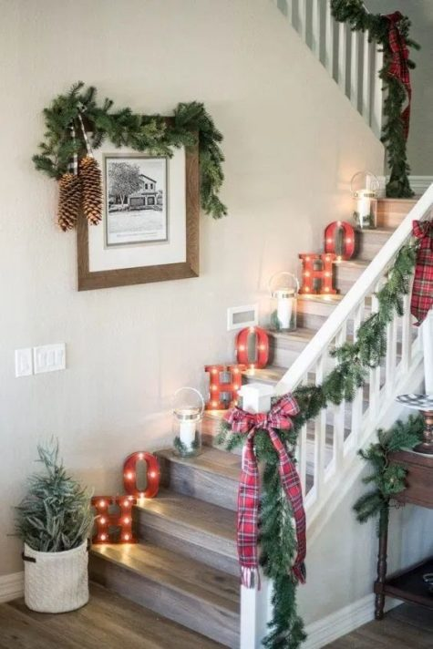 a farmhouse holiday nook with evergreens, plaid bows, pinecones and candle lanterns plus marquee lights
